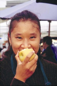 Girl eating apple at farmer's market